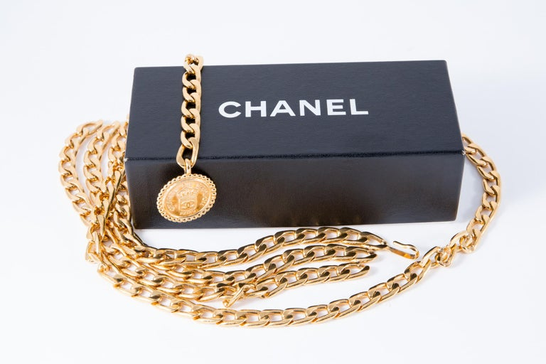 """Gorgeous Chanel gold tone chain belt featuring  a long chain, logo round metal medal """"Chanel"""", with a hook to be adjustable, Chanel pitted back medal. Delivered in original box. Length Maxi: 32.2in. (82cm) In excellent vintage condition. Made in"""