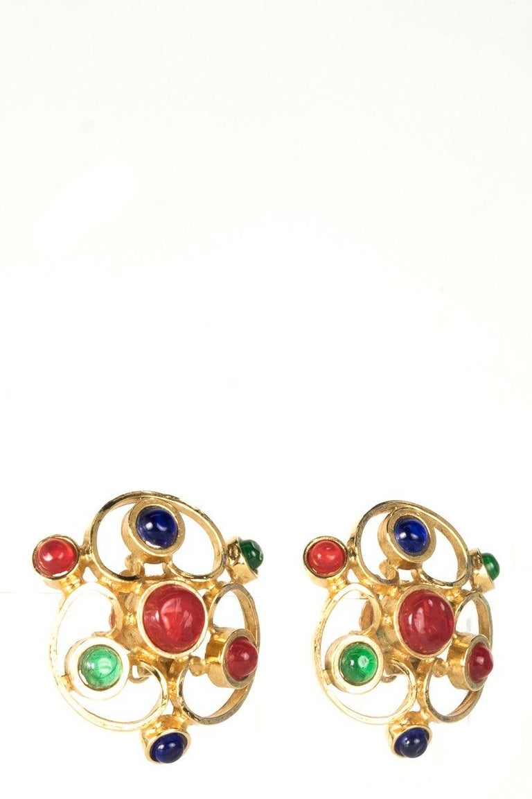 Chanel gold-tone Gripoix earrings featuring cabochons in ruby, emerald and sapphire and clip on closures.     Minor scuffing.