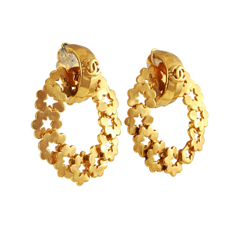 These authentic Chanel Gold Wreath Earrings are in very good vintage condition from the mid 1990's.   Gold wreath hoops made of individual star cutouts dangle from a CC huggie.  Clip on style. Made in France.  Pouch or box included.