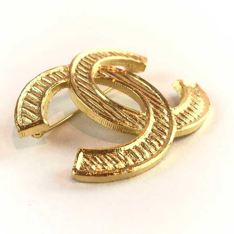 The brooch is from Maison Chanel. It represents the CC of the mark in gilded metal and streaked with fine gold. The brooch has never been worn. It is 6 centimeters long by 4 centimeters wide. Presence of the mark indicating that it comes from the