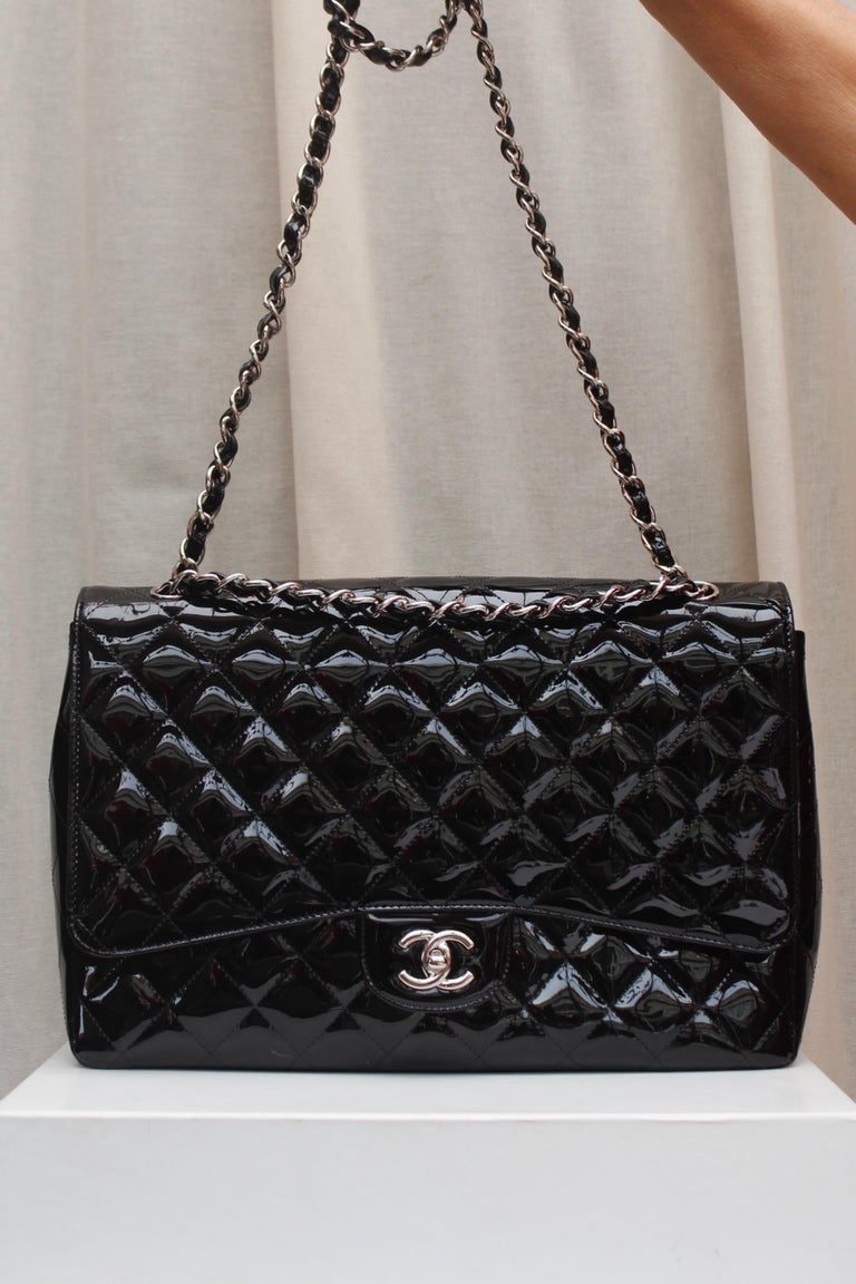 CHANEL (Made in Italy) Gorgeous large black quilted patent leather. It can be worn over the shoulder or cross-body, thanks to two silver plated shoulder straps entwined with black patent leather. One patch pocket at the back. Silver plated