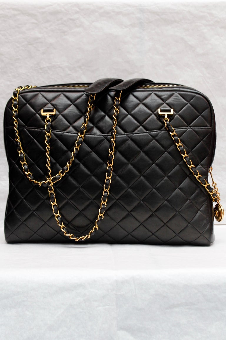 CHANEL (Made in France) Gorgeous camera bag in black quilted lambskin with gilded metal hardware, featuring one patch pocket on each side. It can be worn over the shoulder or cross-body thanks to a double chain entwined with black leather, and two