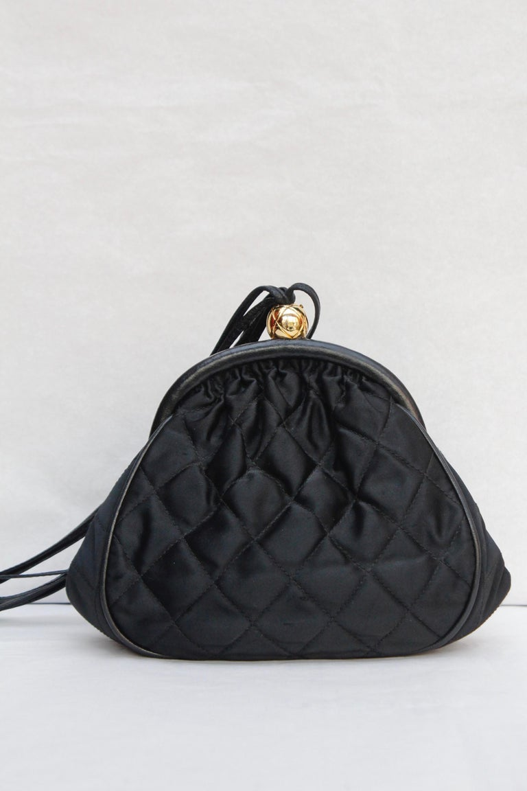 CHANEL (Made in Italy) Gorgeous small evening bag composed of quilted black satin, trimmed with leather edges. It opens with a gilded metal toggle closure in the shape of a quilted ball engraved with a CC logo. It can be worn cross-body or over the