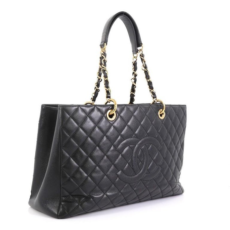 This Chanel Grand Shopping Tote Quilted Caviar XL, crafted in black quilted caviar leather, features woven-in leather chain straps with leather pads, stitched CC logo, exterior back pocket, and gold-tone hardware. It opens to a black satin interior