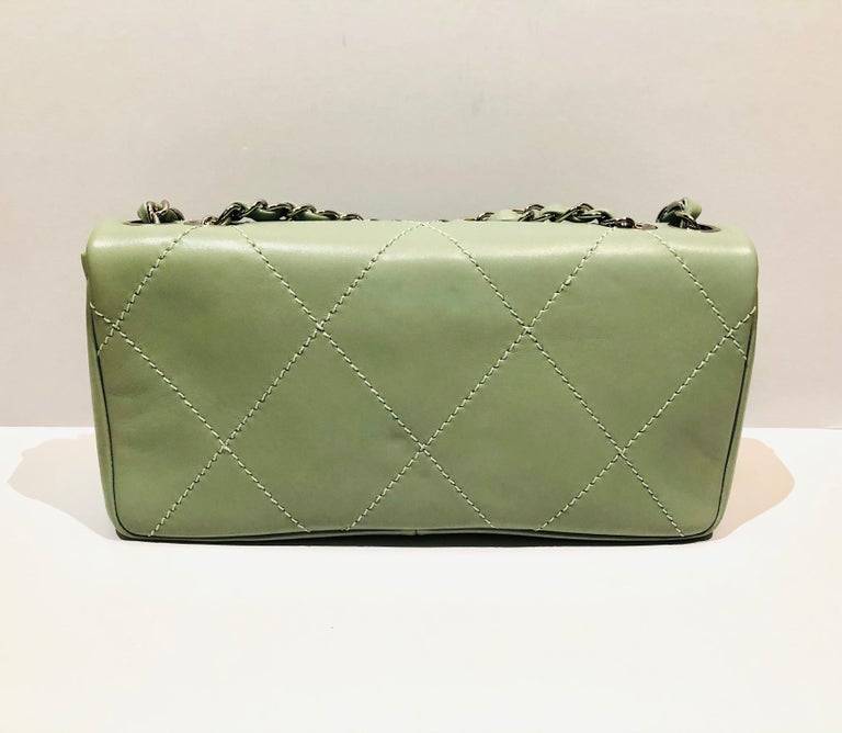 """- Chanel green """"CC"""" silver hardware shoulder bag.   - White stitching from front to back.   - Silver chain strap.   - """"CC"""" silver hardware flap closure.   - Chanel nylon lining.   - Serial no: 9710783 from year 2004 to 2005.   - Length: 25cm.  -"""