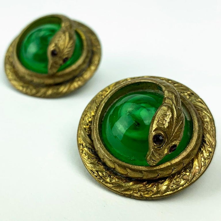 The earrings are from Maison CHANEL. These are two balls of green glass paste, each encircled by a cobra metal hammered and gilded with fine gold. The earrings are in very good condition. We have here an exceptional piece knowing that the clips go