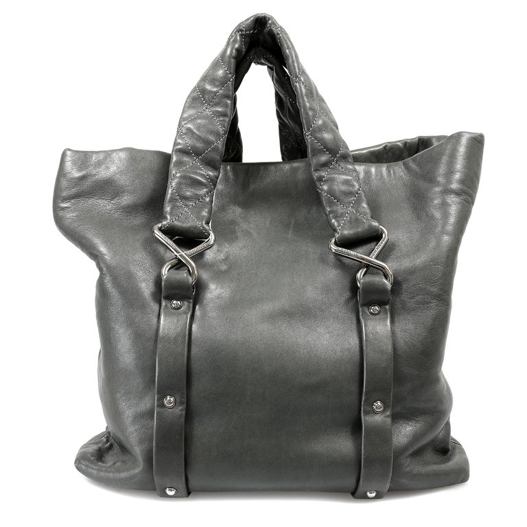 This authentic Chanel Grey Lambskin Eight Knots Tote is in pristine condition.  The iconic style is a great bag for daily use without sacrificing an ounce of style. Dark grey supple lambskin tote has a roomy front pocket quilted in contrasting light