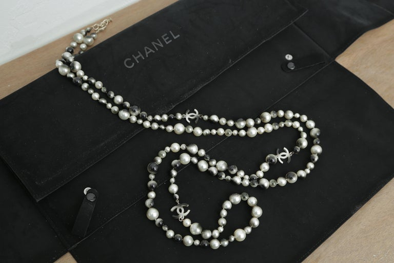 This elegant extra long necklace is crafted of smooth bi-colored faux pearls of various sizes and a dark silver Chanel Cc logos.  This necklace is long enough for triple strand. 32