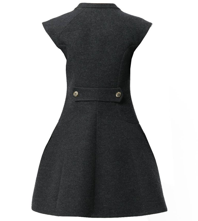 Beautiful Chanel grey silk blend vest-overcoat dress. It features a v-neck, a shawl lapel, a front button fastening, cap sleeves, side slit pockets, a flared style, a mid-length, a back buttoned strap and gold-tone and silver-tone flower embellished