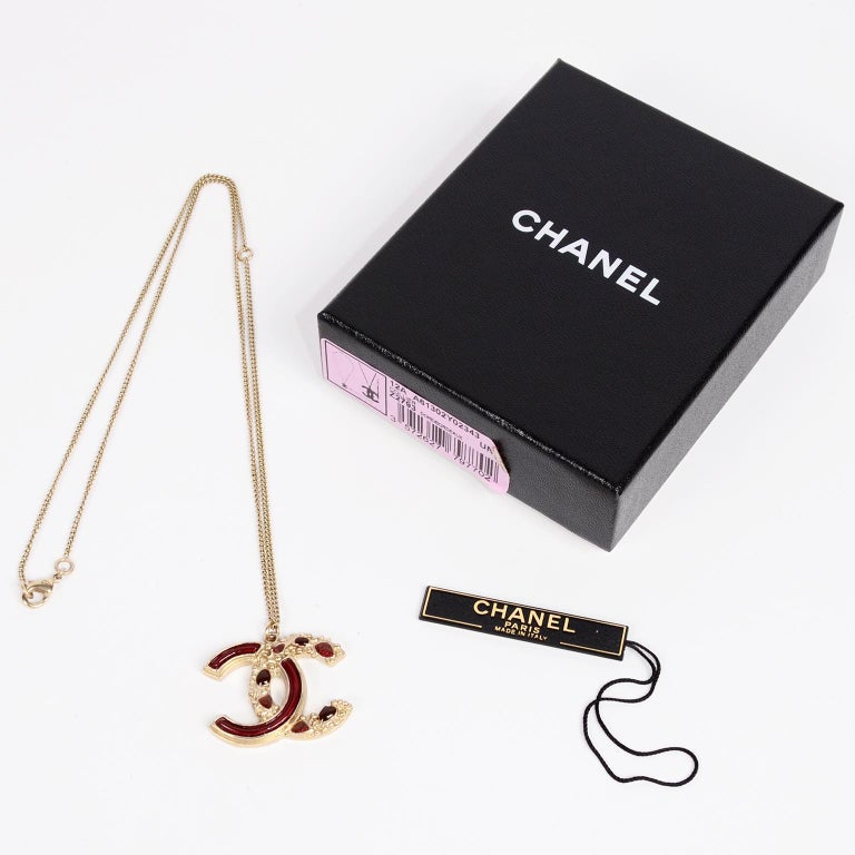 This is a gorgeous Fall 2012 Chanel CC Pendant Necklace with its original box and tag.  The back of the CC logo is a sparkle maroon and the front has the same maroon with the second C having individual gripoix (poured glass) stones filled into the
