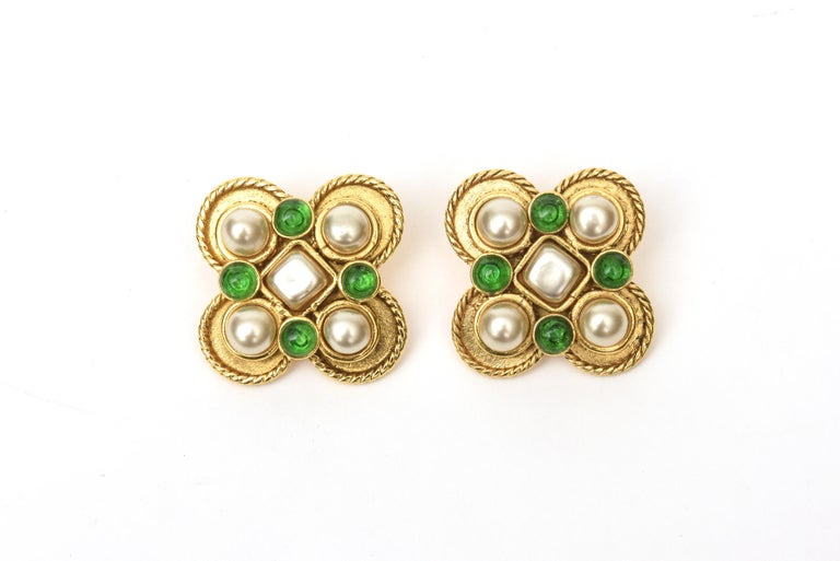 These stunning pair of Chanel Gripoix green glass and faux pearl clip on earrings are from the 90's. They have a stately look on the ear lobe. The twisted gold metal in rope design accents the colors and materials. These can go day to evening and