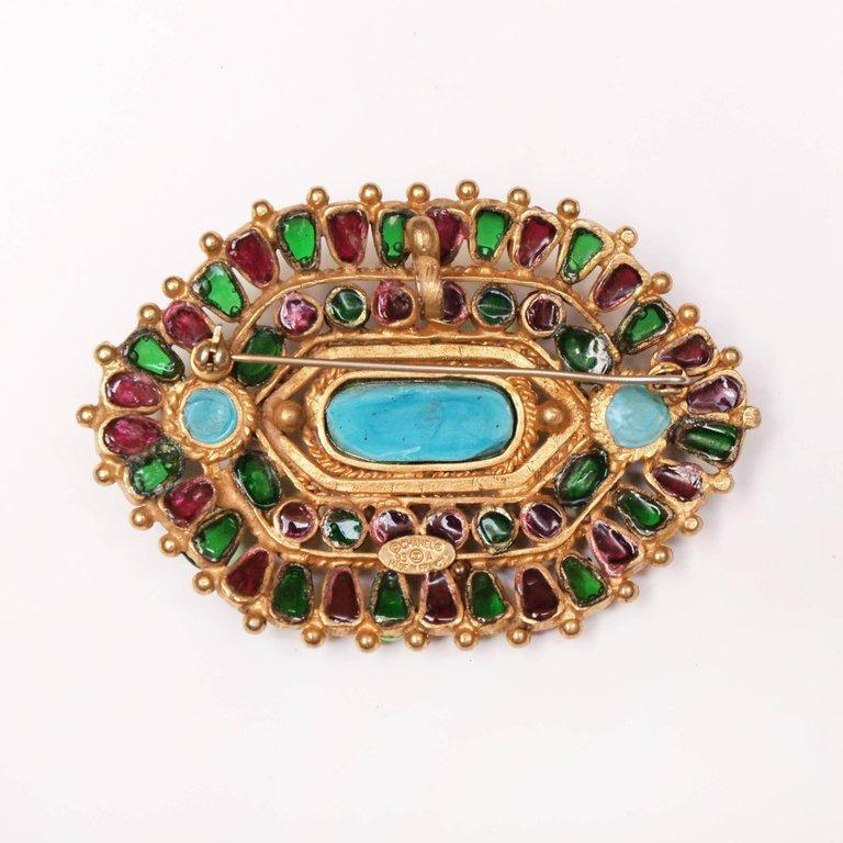 A rare Chanel brooch which has multi color Gripoix glass stones and pate de verre set in a matte gold open work pattern. There is also a hook so it can be worn as a necklace . A stunning piece of Chanel collectable jewellery.