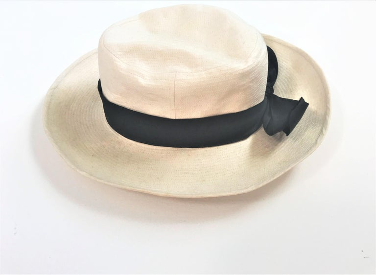 Chanel hat made of beige cotton garnished with a black 4 cm wide black sattin ribbon with a bow. The entire hat is sepped all around like a straw hat with a 1/2 cm wide seam. Measurement: Head size 59, border width 8 cm, head height 9 cm with a 4 cm
