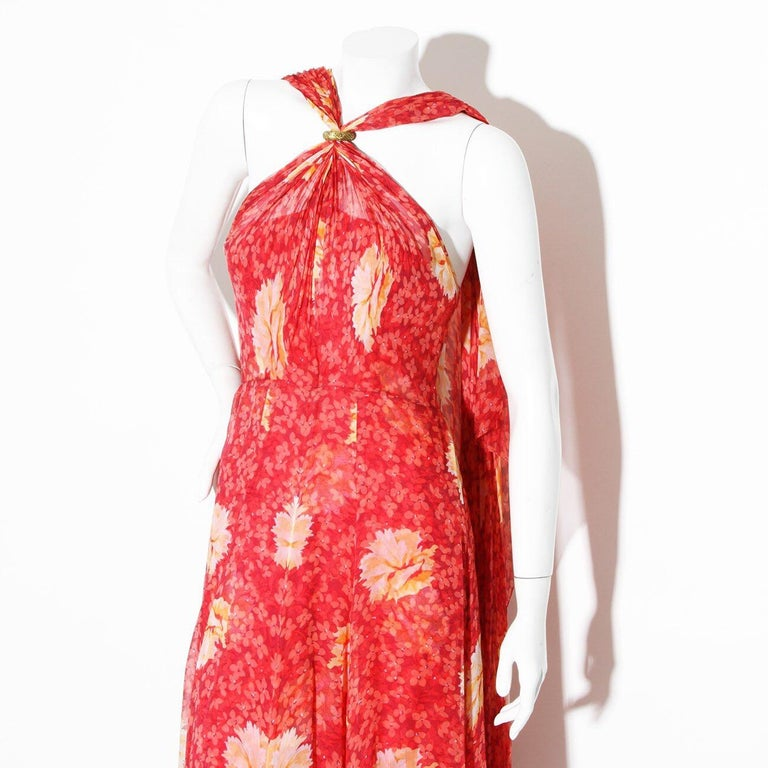 Product Details: Vintage Haute Couture chiffon gown by Chanel Lifetime Chanel Piece  Late 60's Early 70's  Halter top with gold clasp closure  Clasp that holds halter is signed by Robert Goossens   Bias cut chiffon fabric Floral Print  Zipper