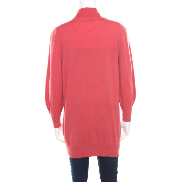 This Chanel cardigan blends comfort and style perfectly! Lovely in hot coral, this cardigan is made of 100% cashmere and features a V-neckline, front button fastenings, long sleeves, and twin slip pockets. It is one creation your wardrobe definitely