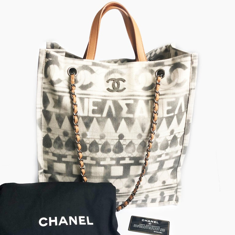 Authentic, preowned Chanel Iliad Large Tote Bag from the 2018 Cruise Collection, featuring Greece antiquities and modernity.  Made from canvas with leather top handles and removable chain & leather shoulder straps.  Lined in beige canvas with one