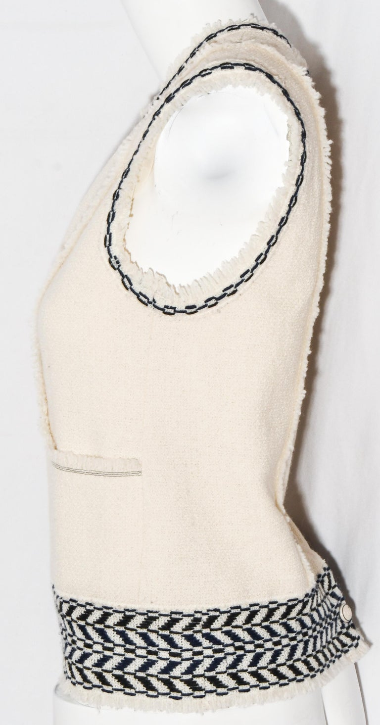 Chanel woven ivory wool sleeveless top features contrasting chain link stitch detailing in black and navy around round neckline and armholes.   With frayed fringe trim, around neckline and armholes but, also, including this trim on the hem and the