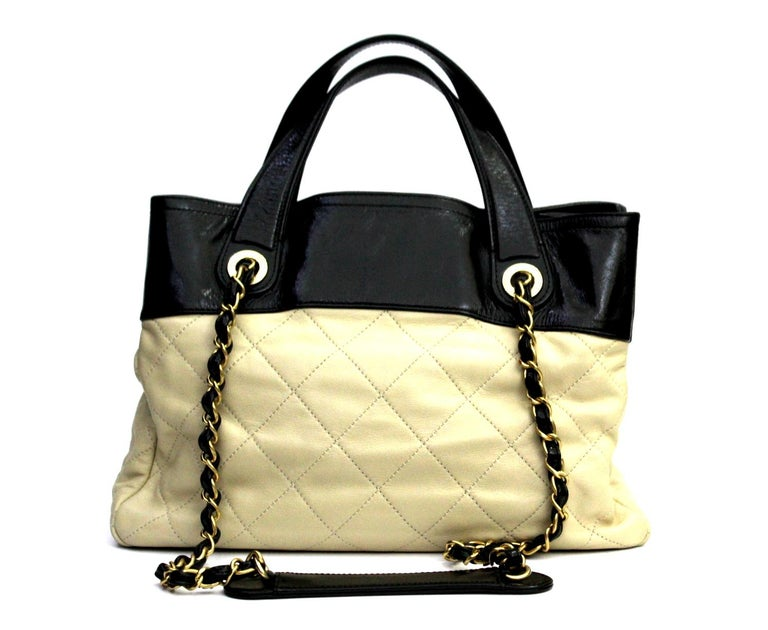 This designer vintage shoulder bag in quilted nude lambskin and black aged calfskin with CC logo lock at the front and gold tone hardware from 2012 Collection is perfect for a casual wear. It has a roomy interior with two open compartments, one