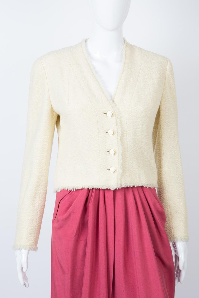 Chanel  ivory and lurex tweed wool boucle jacket 2000s Croisiere featuring a short fitted shape, a back gilet slit detail, front fancy camelias buttons, fringed edges, an ivory silk lining, and a silver hardware chain in the bottom lining. Label