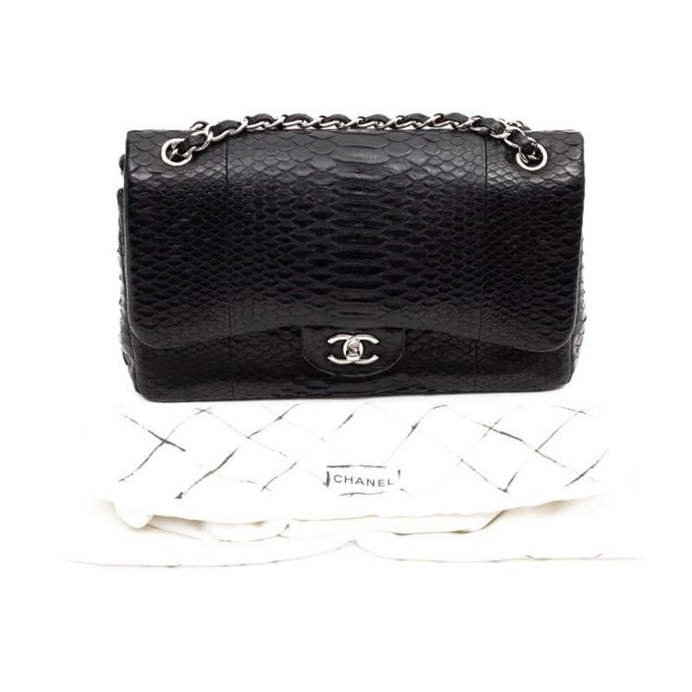 Beautiful CHANEL piece Jumbo model with double flap in black python. The jewelry is made of palladium silver metal and the chain is interlaced in python. It is lined with smooth black leather. It has a large storage space with three pockets, one of