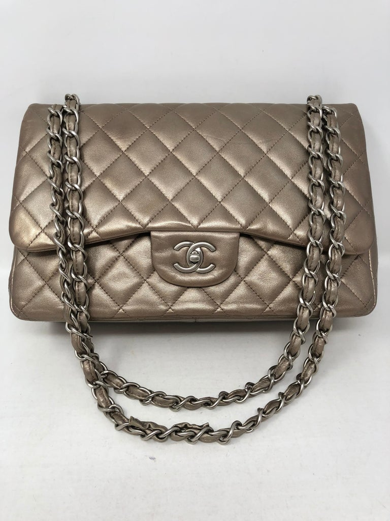 Chanel Jumbo Bronze Metallic in lambskin leather. Beautiful neutral color for all seasons. Silvertone with bronze color. Silver hardware. Good condition on exterior. Inside pocket has a slight tear. Bag can be worn doubled or as a crossbody.