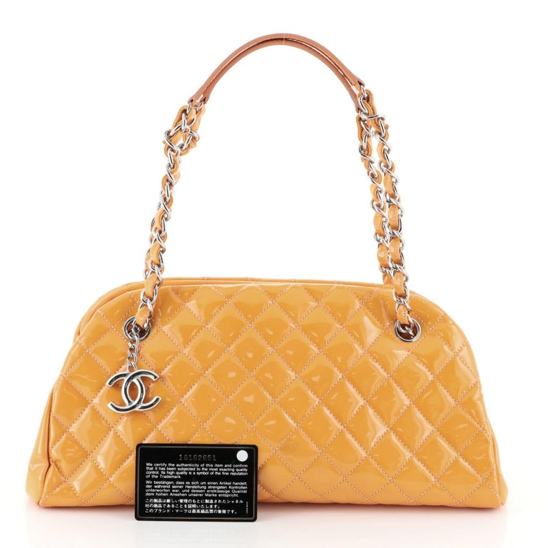 This Chanel Just Mademoiselle Bag Quilted Patent Medium, crafted from orange quilted patent leather, features woven-in leather chain straps with leather pads and silver-tone hardware. It opens to a pink fabric interior with two side compartments and