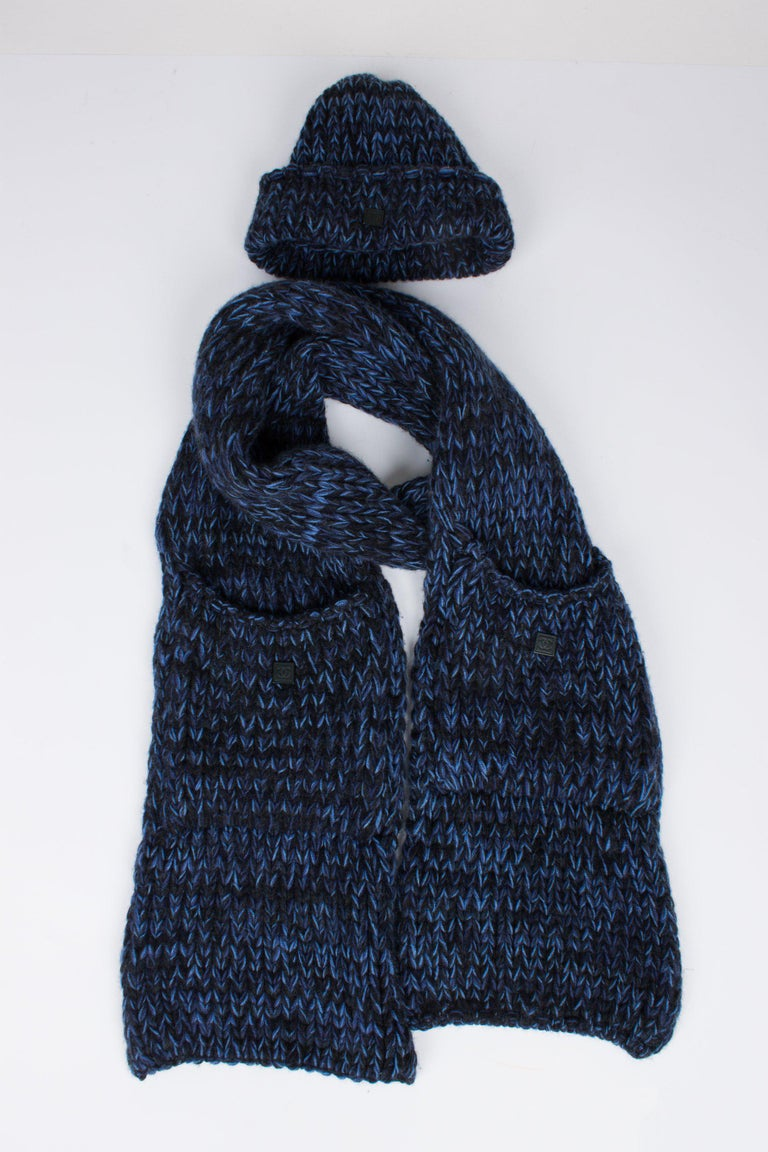 Two-piece Chanel set; a knitted hat and a scarf, both in a chunky crochet knit in black and blue cashmere. The hat has a round shape and a fold over where you will find a square black metal tag with CC-logo.  The scarf has an enormous length, it