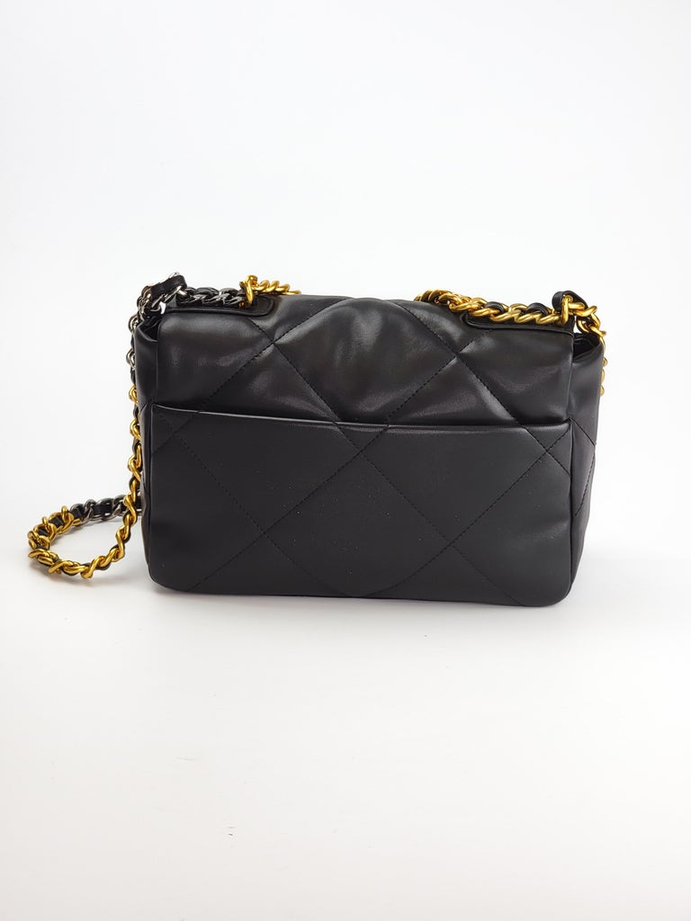 This Chanel handbag is made with supple lambskin quilted leather in black.  The bag features signature diamond stitching, gold and sliver tone hardware, a front flap with the signature interlocking CC turn lock closure, a metallic chain strap