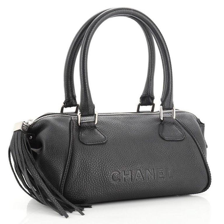 This Chanel Lax Tassel Bag Pebbled Leather Medium, crafted from black pebbled leather, features dual rolled handles, leather tassel, stamped Chanel logo, and silver-tone hardware. Its zip closure opens to a black fabric interior with side zip