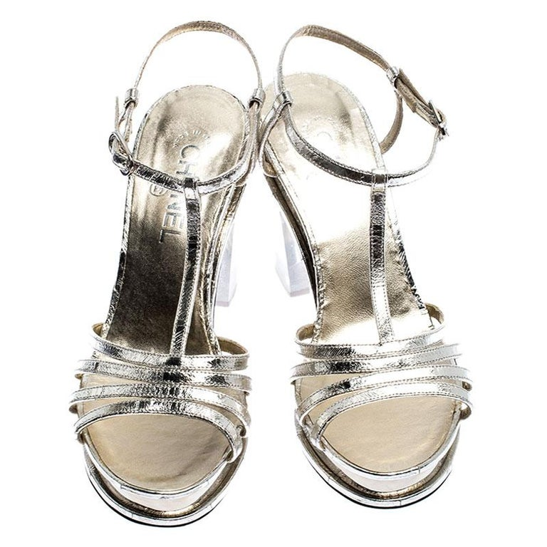 Chanel's designs come with a style that leaves all in awe. Take a look at these sandals! They've been crafted from light gold metallic leather in a strappy layout and styled with the signature CC. The pair is complete with ankle fastening and 10 cm