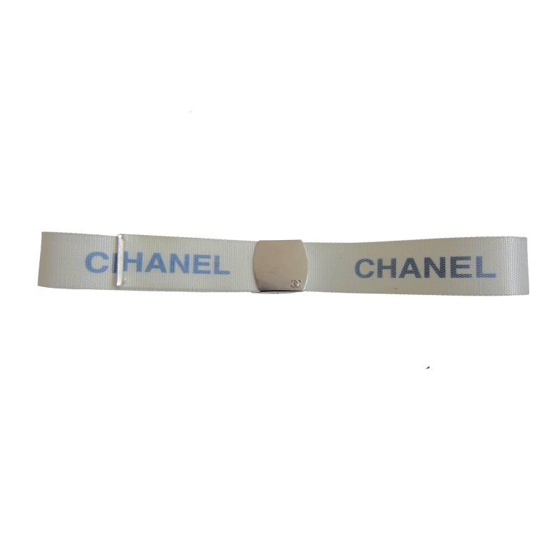 Chanel military style white nylon belt with blue logos from circa 90s. Silver tone metal logo buckleIt, can be adjusted to fit any waist size.  Total length with buckle : 85. 5 cm