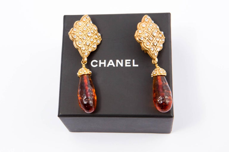 1980s Chanel embellished clip-on earrings featuring a amber color glass bead, glass strass embellishments and gold-tone hardware.   Chanel signature plaque on the reverse of the earrings .  Maxi Length: 3,1in. (8cm) In excellent vintage condition.