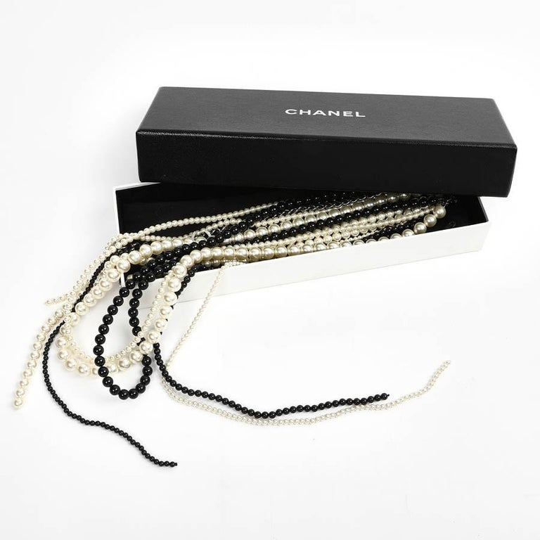 Delightful Chanel necklace made of pearly beads of 2 colors. There are 2 chains that end with two double