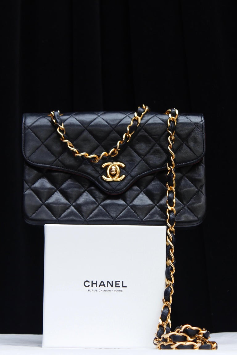 CHANEL PARIS (Made in France) Lovely shoulder bag in quilted black lambskin with gilded metal hardware. It opens with a CC turn lock. It can be worn over the shoulder or cross-body thanks to a long chain entwined with black leather. Burgundy