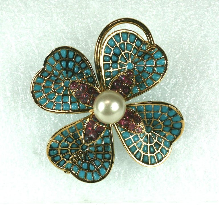 Chanel 1950 clover brooch. Clovers are another motif Chanel has revisited many times since the 1930s. This elaborate dimensional brooch derives from the Gripoix workshops in Paris. Pale turquoise and pale ruby poured glass enamel is set into a