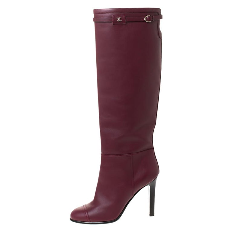 Your winter wardrobe would take an all-new shape by adding these stunning knee-length boots by Chanel. These are classic leather boots featuring a maroon shade coupled with buckled straps at the top which is also detailed with a CC logo. Adding to