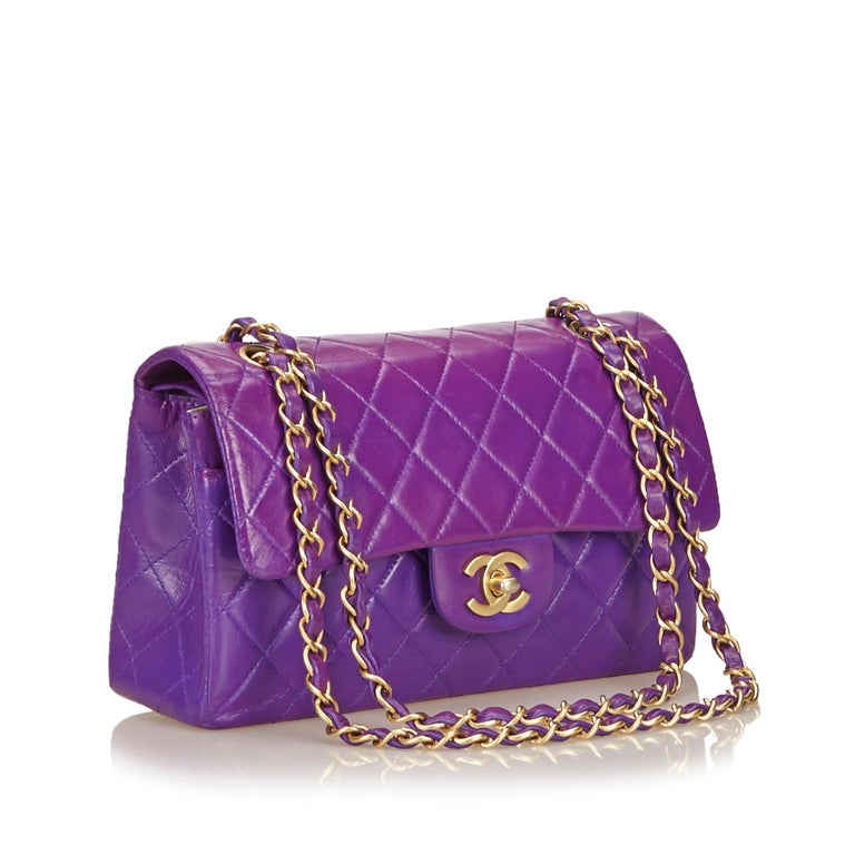 This Chanel Classic Double Flap in purple features a quilted lambskin leather body, gold-tone hardware, chain shoulder straps, an exterior back slip pocket, double front flaps with interlocking Cs and a twist-lock closure, and interior open