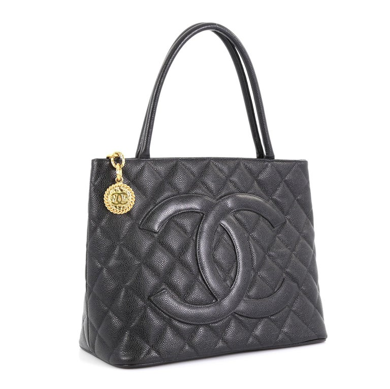 This Chanel Medallion Tote Quilted Caviar, crafted from black quilted caviar leather, features dual rolled tall handles, oversized stitched CC logo, and gold-tone hardware. Its zip closure opens to a black leather interior with slip and zip pockets.
