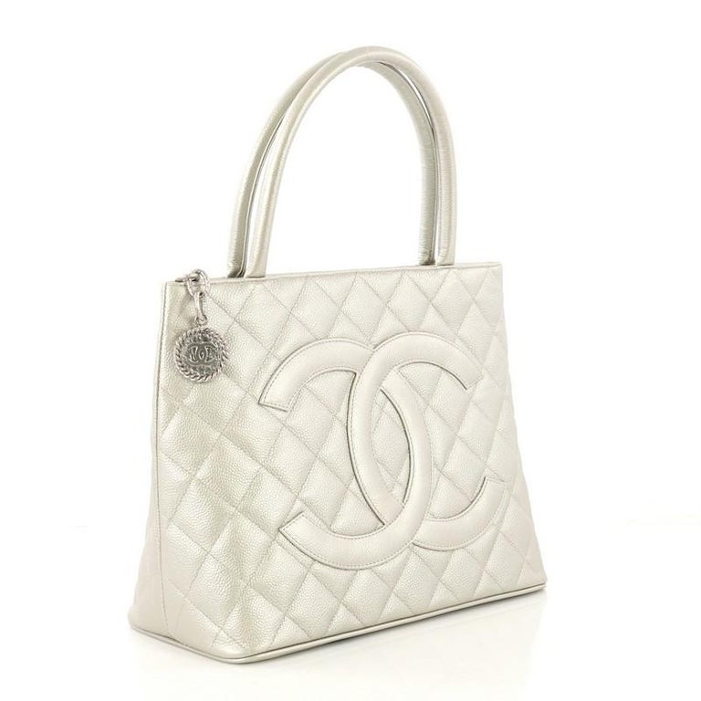 This Chanel Medallion Tote Quilted Caviar, crafted from silver metallic quilted caviar leather, features dual rolled tall handles, oversized stitched CC logo, and silver-tone hardware. Its zip closure opens to a silver metallic leather interior with