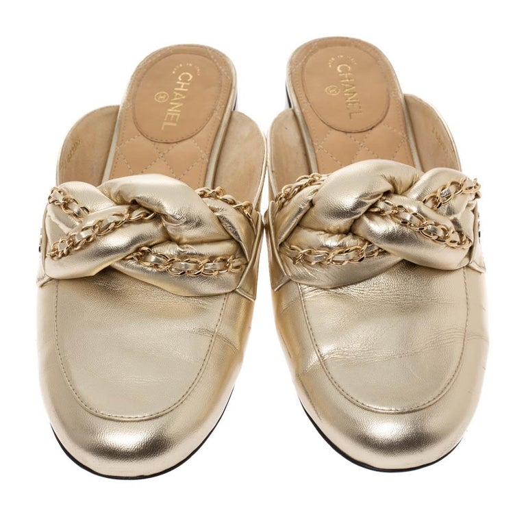 These mules from Chanel are designed for the fashionable you! Metallic gold leather is used to create these round toe mules and the leather and chain knotted details on the vamps lend them a distinctive look. The comfortable insoles will ensure you