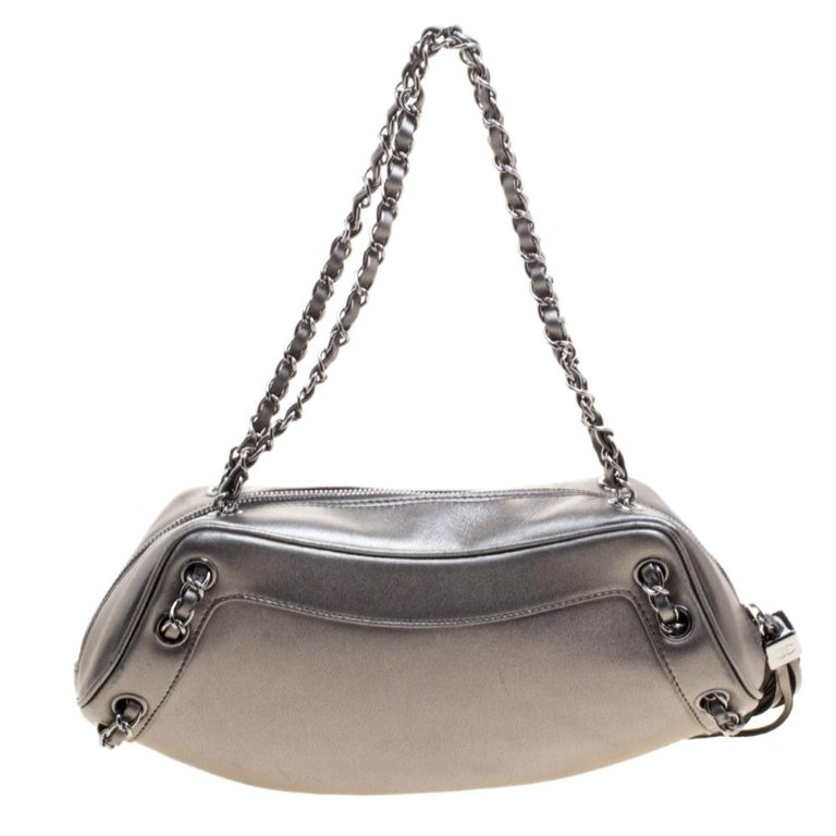 Get evening-ready with this exquisite creation from the house of Chanel. Featuring a unique structure, this bag is designed in a metallic grey leather body and detailed with a playful tassel on the side. Ideally proportioned to stow just essentials,
