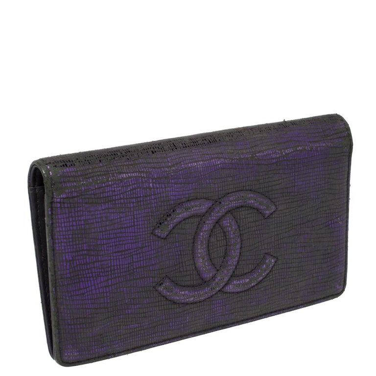 This Chanel bifold wallet is designed for making a statement. Crafted from leather, it has a metallic purple exterior and flaunts the iconic CC logo detailing on the front flap. It opens to a leather interior housing a zip pocket, slip pockets, and