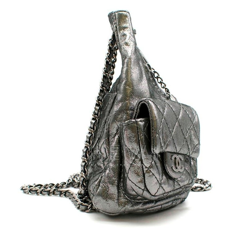 Chanel Mini Silver Split-Zip Backpack  -Dark silver, glitter-effect fabric  -Gunmetal hardware -Chain and woven fabric shoulder strap  -Quilted fabric front cargo pockets, CC press-stud hardware  -Back-zip pocket  -Front split-zip closure  -Black