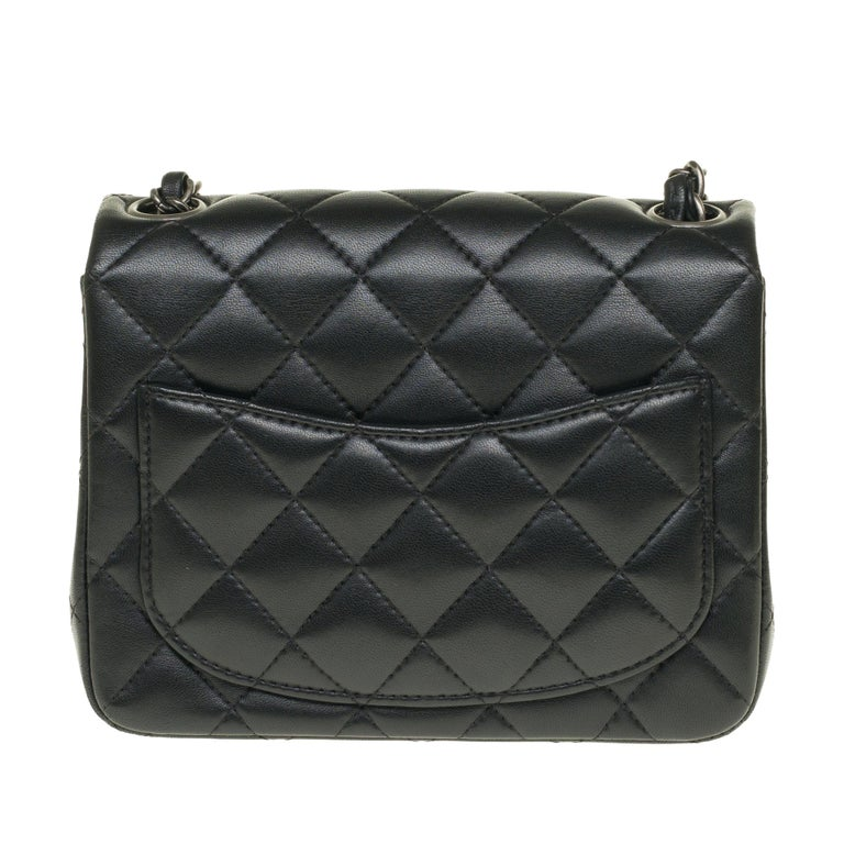 Beautiful Chanel Mini Timeless handbag in black nappa leather, chain handle intertwined with black leather allowing a hand or shoulder or shoulder strap.  Silver metal flap closure. A patch pocket on the back of the bag. Lining in black leather, one