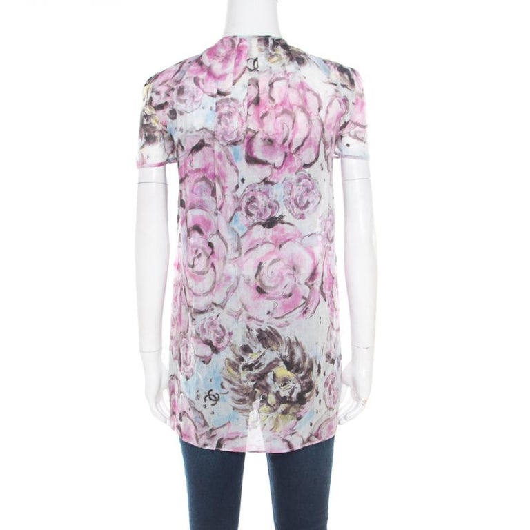 How lovely is this blouse from Chanel! The multicolour creation is made of 100% cotton and features a floral print all over it. It flaunts an open front silhouette, a neck-tie detailing and short sleeves. It is sure to lend you a flattering fit and