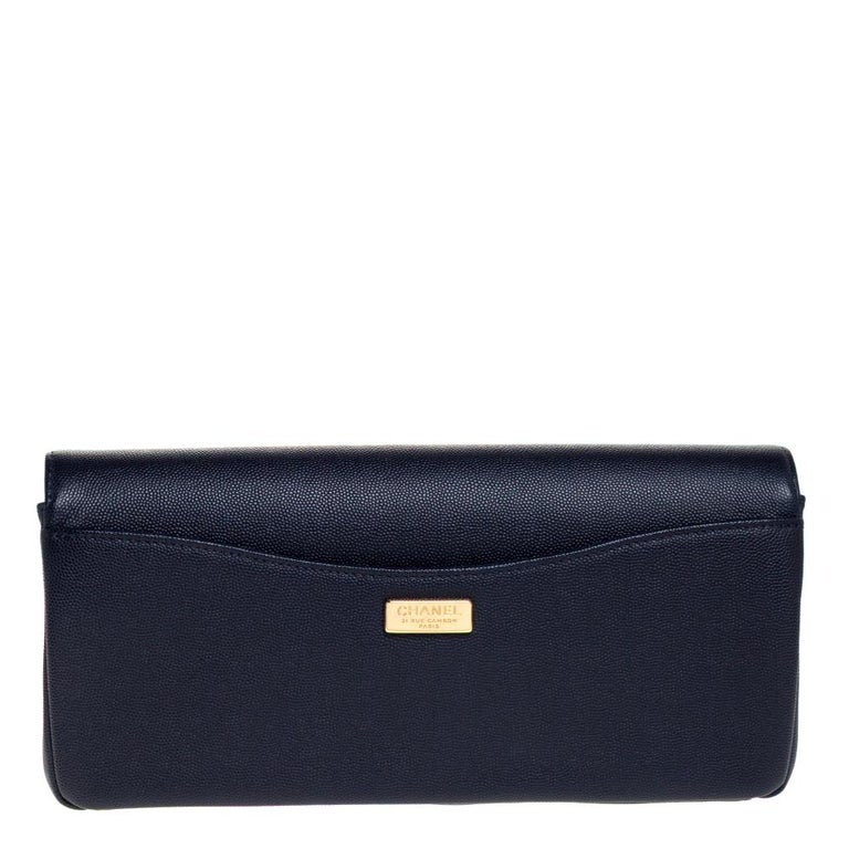 This lovely clutch by Chanel carries an elegant and luxurious design. It will be a head-turning addition to anything you wear it with. It features a front flap accented with contrasting gold trims and the iconic CC turn-lock, a navy blue leather