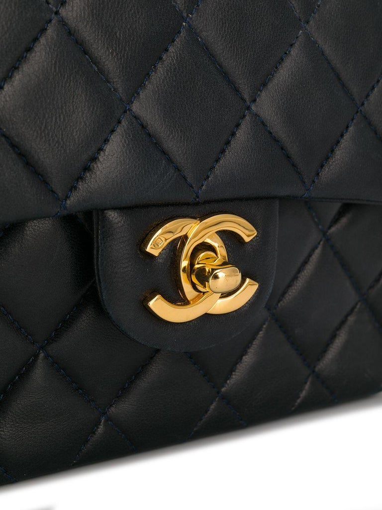 Crafted in France from luxurious calfskin leather in a deep shade of navy, this timeless pre-loved Chanel crossbody bag features a diamond quilted finish, a rear slip pocket and the iconic interlocking CC logo stitched decoratively onto the
