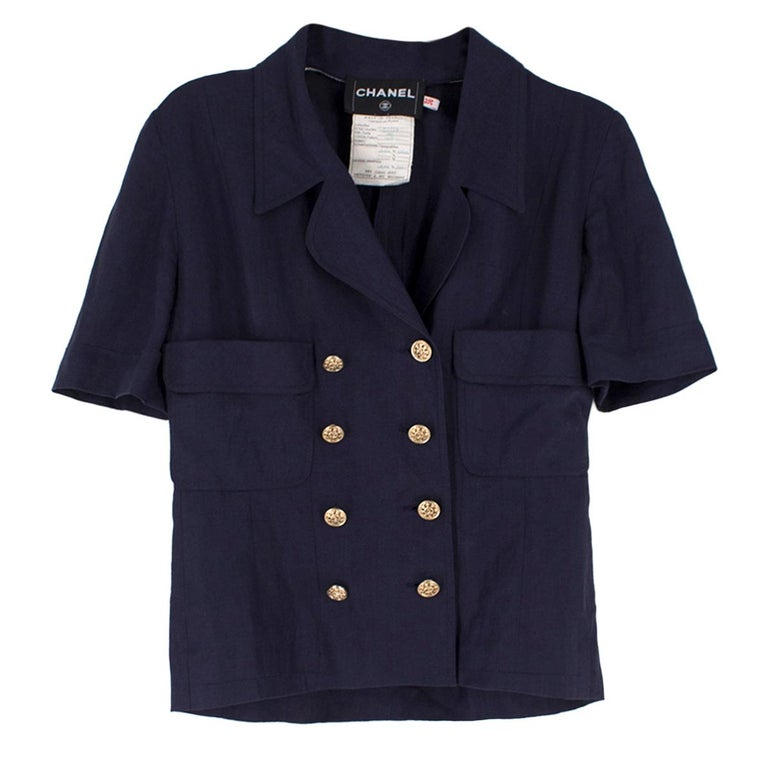 Chanel Navy Wool Short Sleeve Jacket  - Navy jacket - Short sleeved - Notch lapel, double breasted  - Gold toned buttons  - Decorative side flap pockets - Unlined  Please note, these items are pre-owned and may show some signs of storage, even when