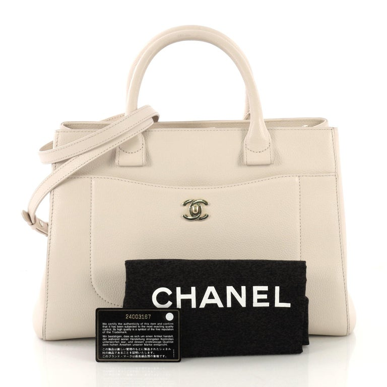 This Chanel Neo Executive Tote Grained Calfskin Small, crafted from white grained calfskin leather, features dual rolled leather handles, front pocket with CC turn-lock closure, and gold-tone hardware. Its magnetic snap closure opens to a white
