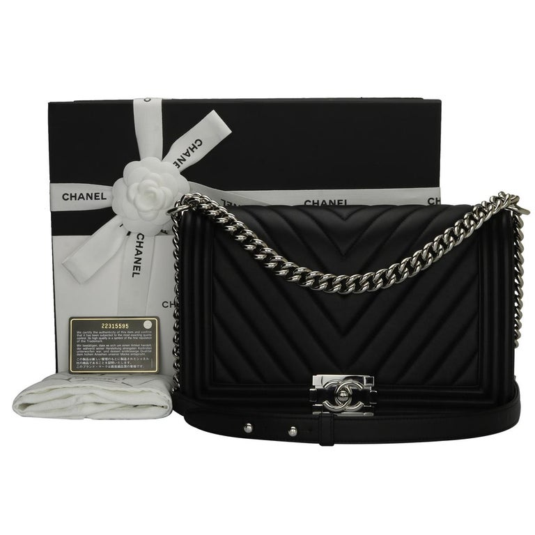Authentic CHANEL New Medium Chevron Boy Black Calfskin with Shiny Silver Hardware 2016.  This stunning bag is still in a mint condition; it still keeps its original shape and the hardware still very shiny, leather smells fresh as if new.  Exterior